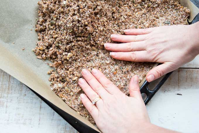 hands pressing down a seed and nut mix onto a baking tray lined with parchment paper