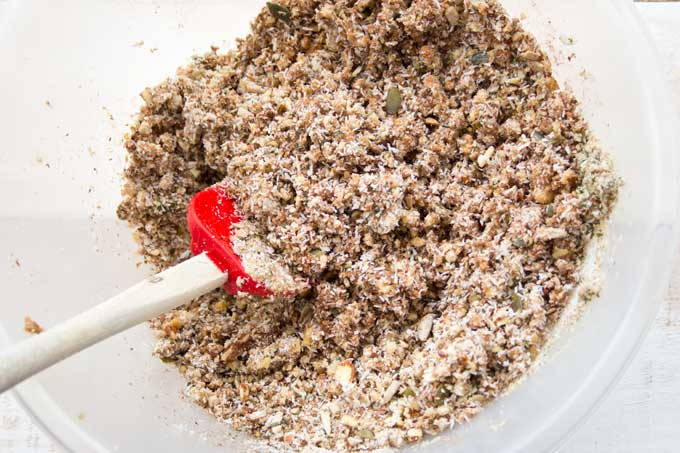 mixing grain free granola in a bowl with a spatula