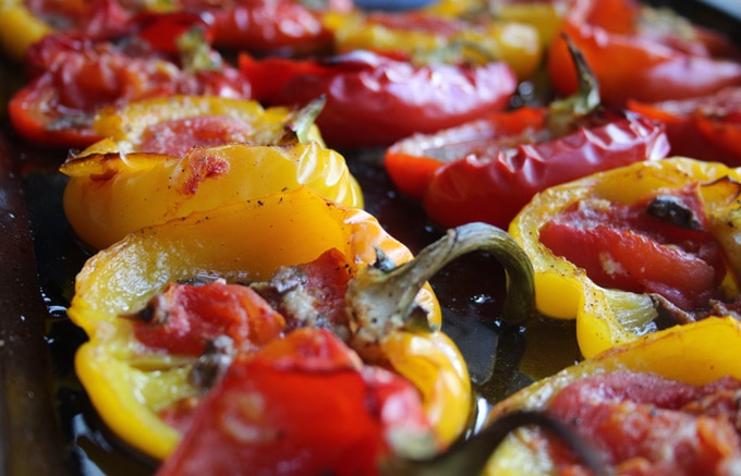 closeup of yellow and red roasted pepper halves filled with tomato, anchovies and garlic on a black baking tray