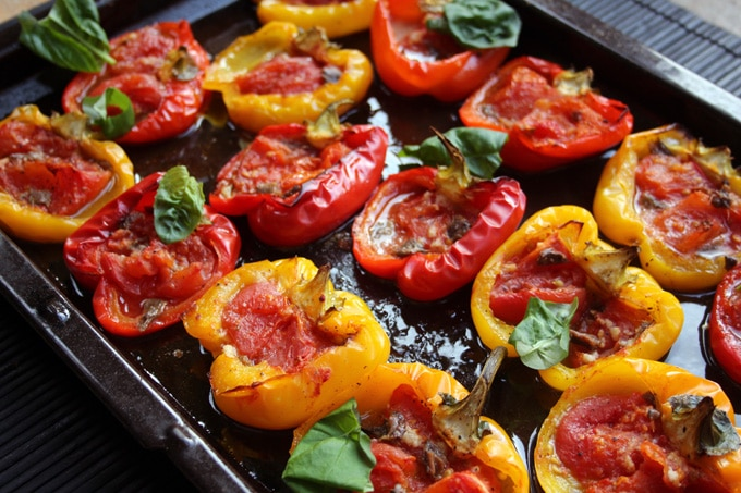 roasted red and yellow stuffed peppers with tomato and fresh basil on a baking tray