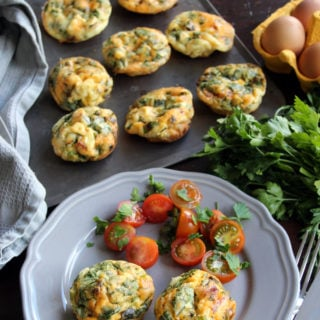 Chorizo Egg Muffins on a baking tray and two muffins with tomato salad on a plate