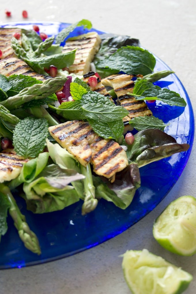 grilled halloumi on a bed of salad with pomegranate seeds