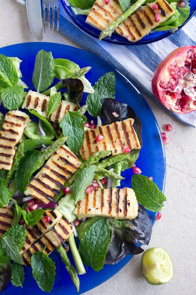 grilled halloumi on a green salad with pomegranate seeds