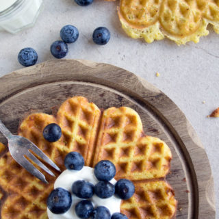heart-shaped waffles on a table decorated with blueberries and a fork