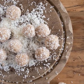 coconut tahini bliss balls on a wooden board