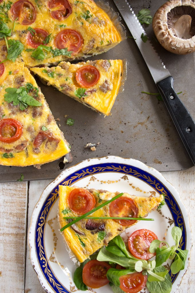 An English breakfast frittata with a knife and a plate on the side