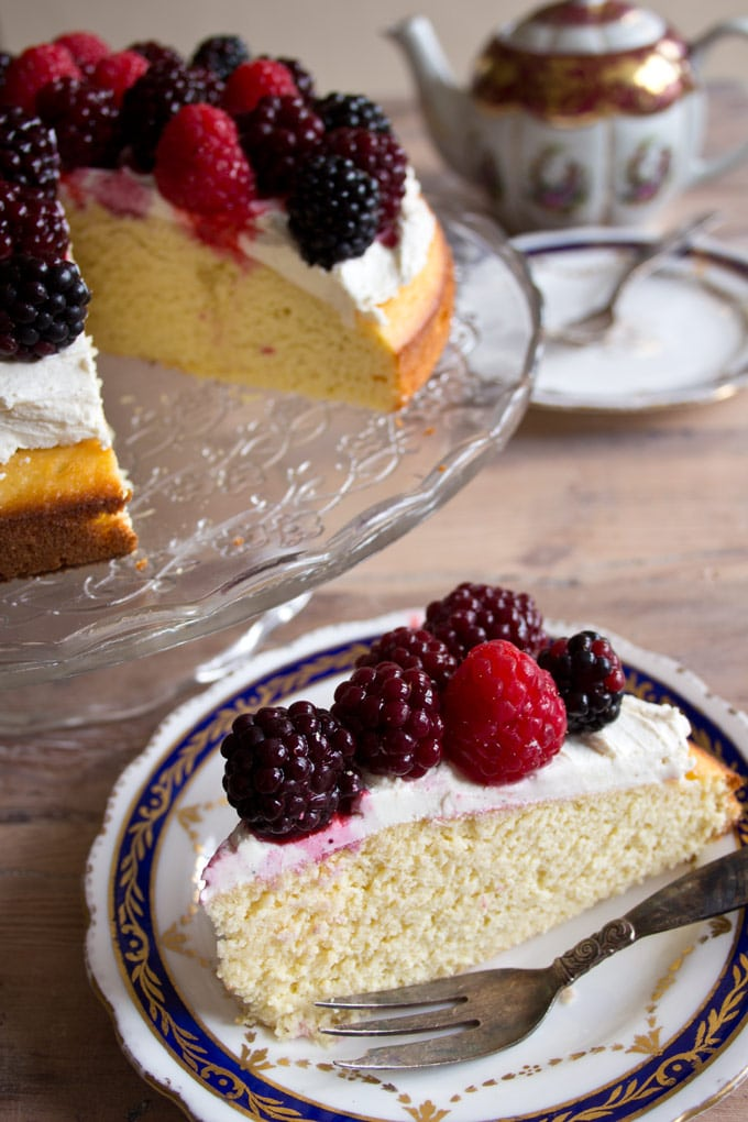 A slice of almond flour cake with mascarpone frosting and berries