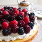 A sugar free almond flour cake decorated with mascarpone frosting and topped with berries