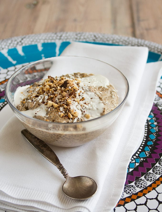 a portion of coffee chia pudding topped with crushed nuts and coconut milk