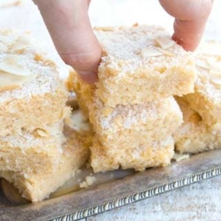 hand lifting a keto blondie from a silver tray stacked with coconut blondies