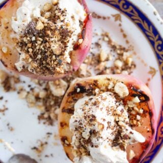 two grilled peach halves topped with mascarpone and hazelnuts