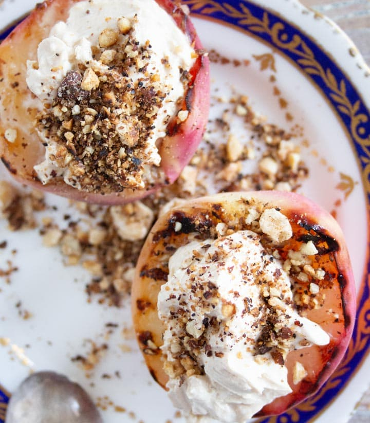 two halves of grilled peaches topped with mascarpone
