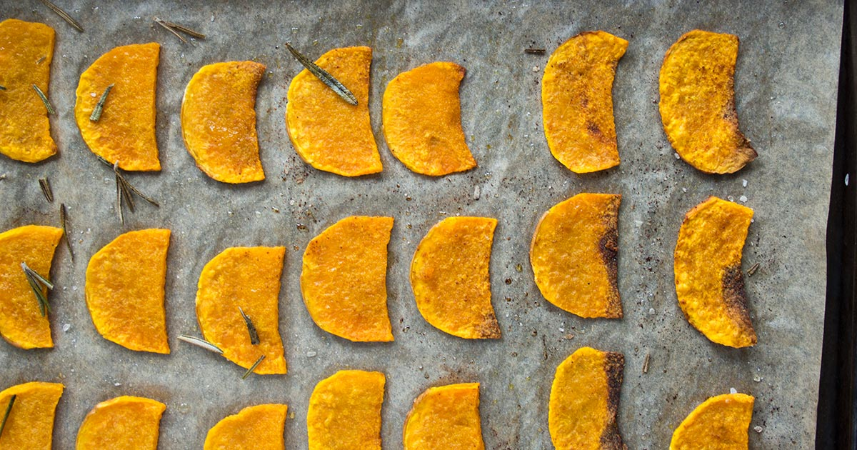 Butternut squash crisps lined up on a baking tray