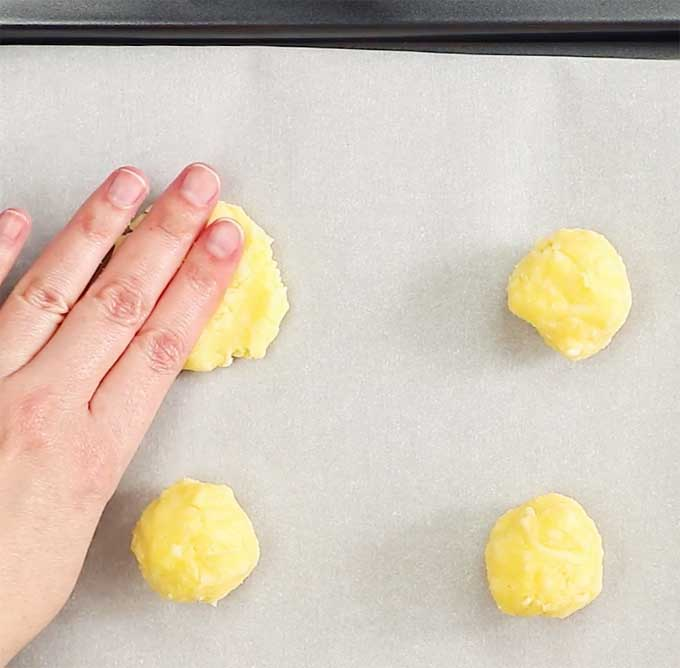 a hand pressing onto dough balls to form flat coconut flour crackers