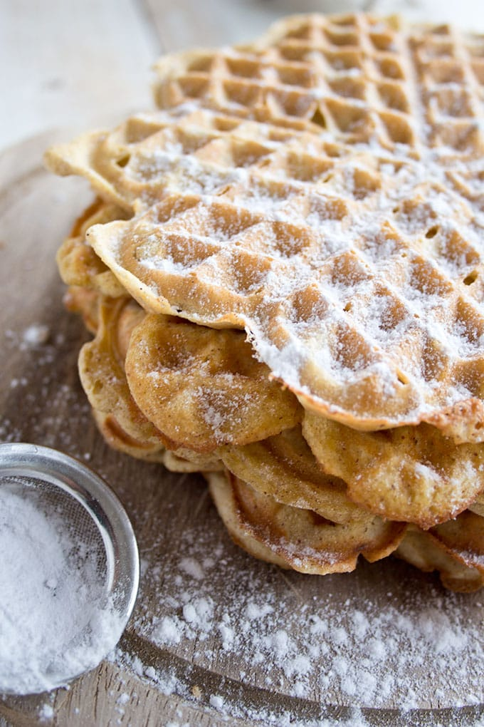 a stack of almond butter coconut flour waffles with a sieve containing powdered sweetener