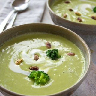 two bowls of broccoli soup with pistachios and broccoli florets