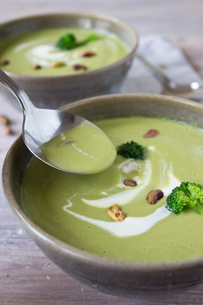 taking a spoonful of broccoli pistachio soup