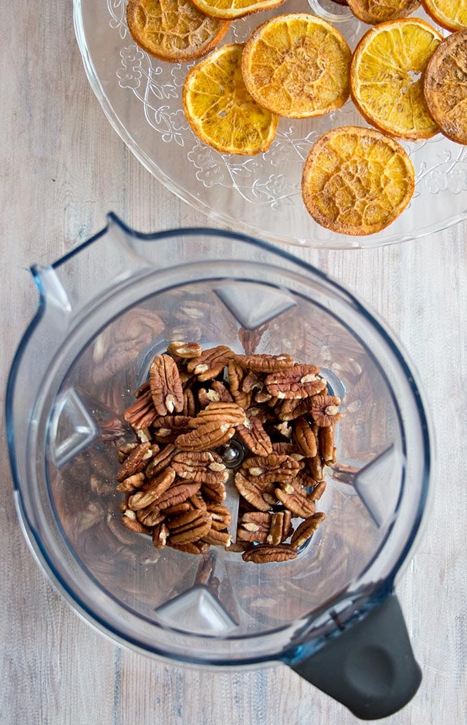 pecans in a food processor and dehydrated orange slices for orange cheesecake