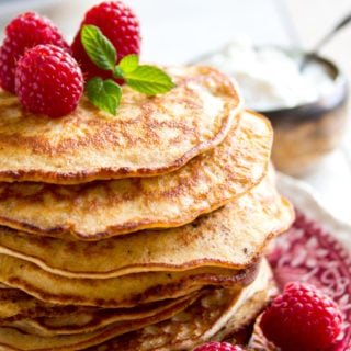 a stack of keto pancakes made with almond flour and cream cheese, decorated with raspberries