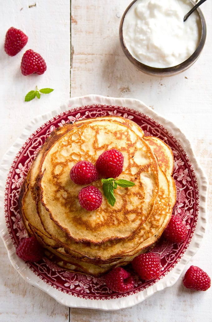 A plate with a stack of almond cream cheese pancakes and a bowl of yoghurt