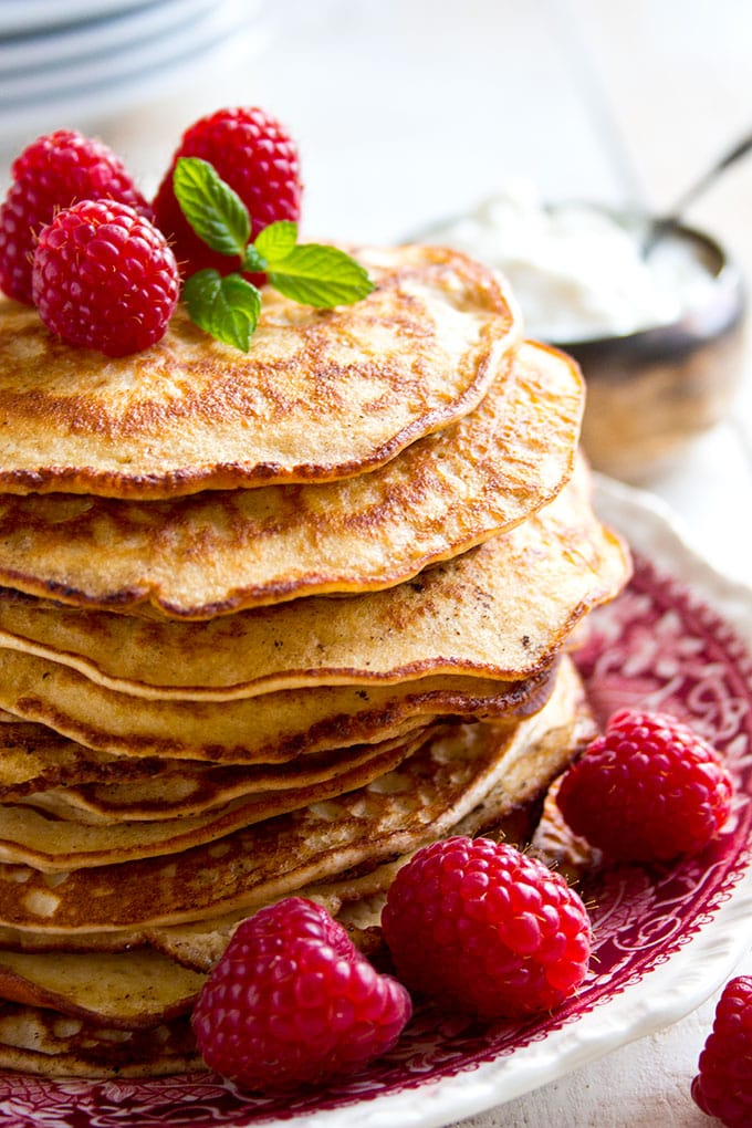 A stack of almond cream cheese Keto pancakes with raspberries on a plate
