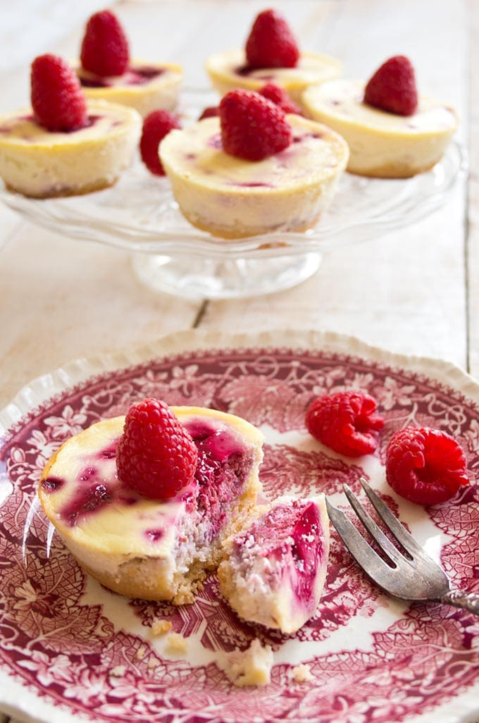 low carb raspberry cheesecake on a plate with a fork and a cake stand with more cheesecakes