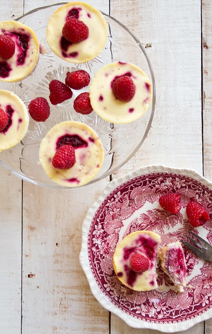 a cake stand with individual low carb raspberry cheesecakes and a raspberry cheesecake on a plate