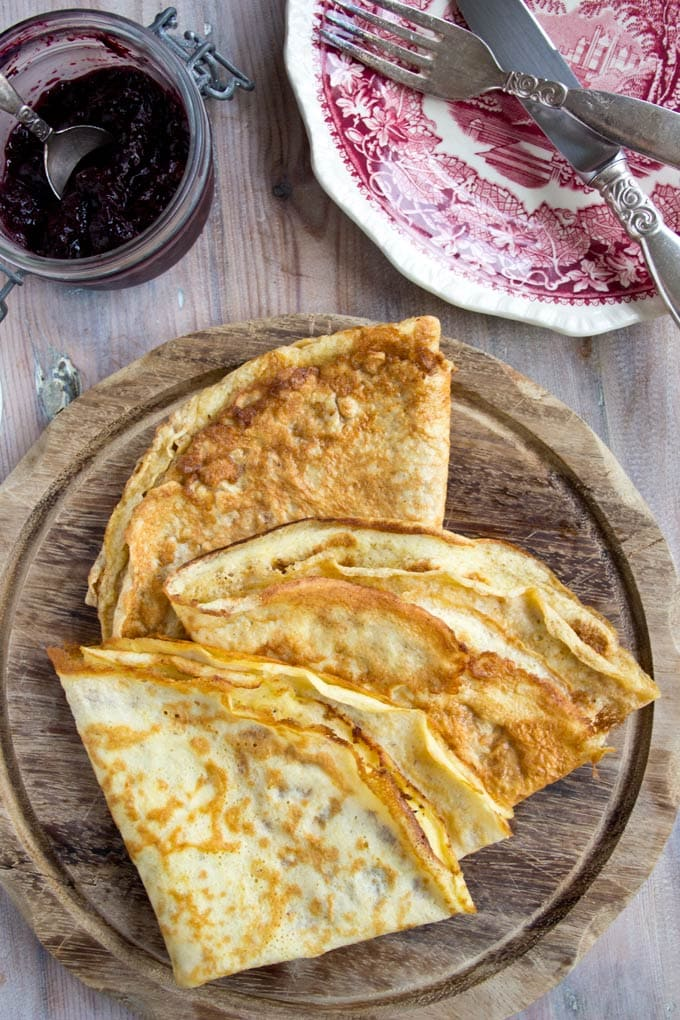 Folded low carb gluten free crepes on a wooden breakfast board with a jar of blueberry jam