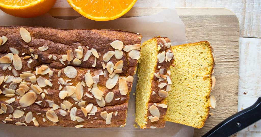 orange almond breakfast cake on a wooden board is made with whole oranges - skins and all. It is low carb, gluten free and sweetened with stevia.