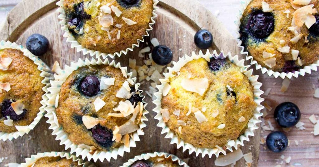 Coconut blueberry muffins topped with coconut flakes