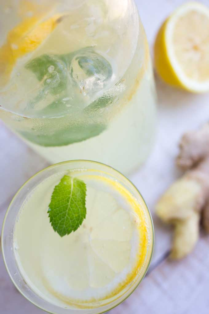 a glass of homemade sugar free ginger ale with ginger and a lemon on the side