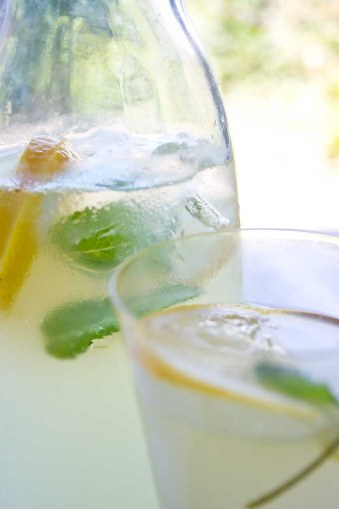 a glass jug of sugar free homemade ginger ale with mint leaves, ice cubes and lemon slices