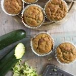 low carb zucchini muffins in paper casings and zucchini being shredded