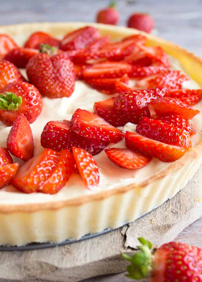 a closeup of a strawberry mascarpone tart decorated with sliced strawberries