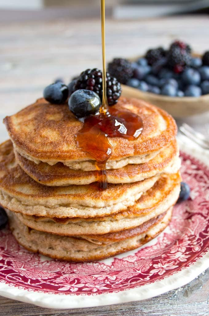 drizzling sugar free syrup over a stack of pancakes on a plate