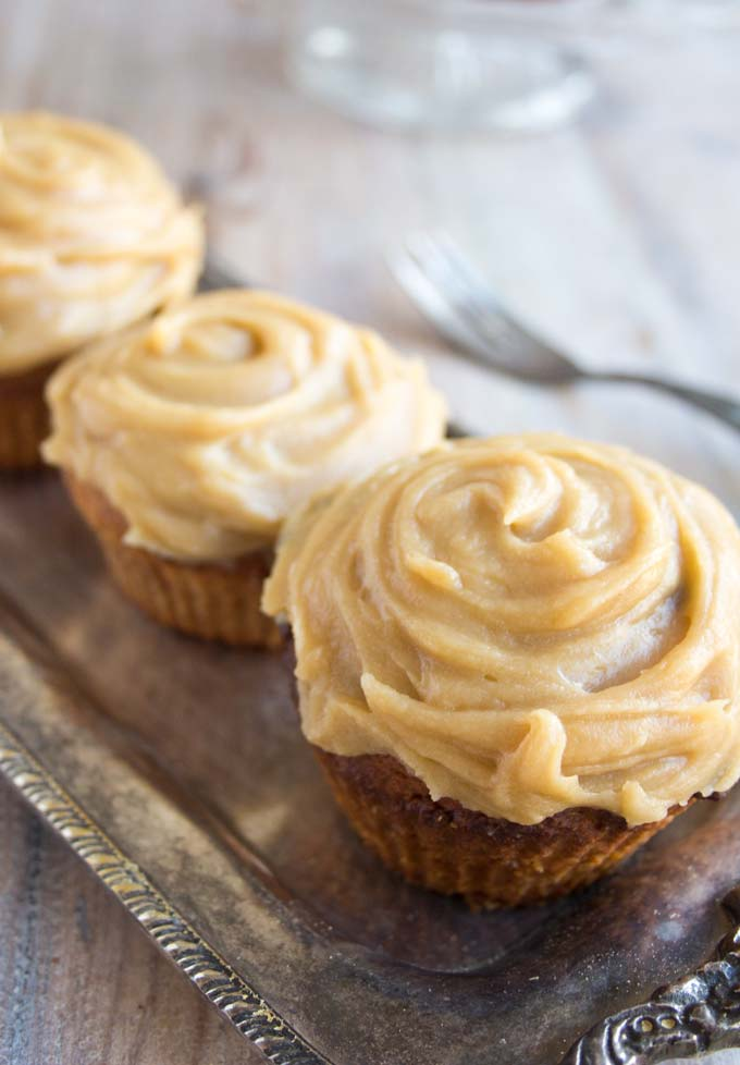 3 low carb gingerbread cupcakes with caramel frosting in a row on a silver tray