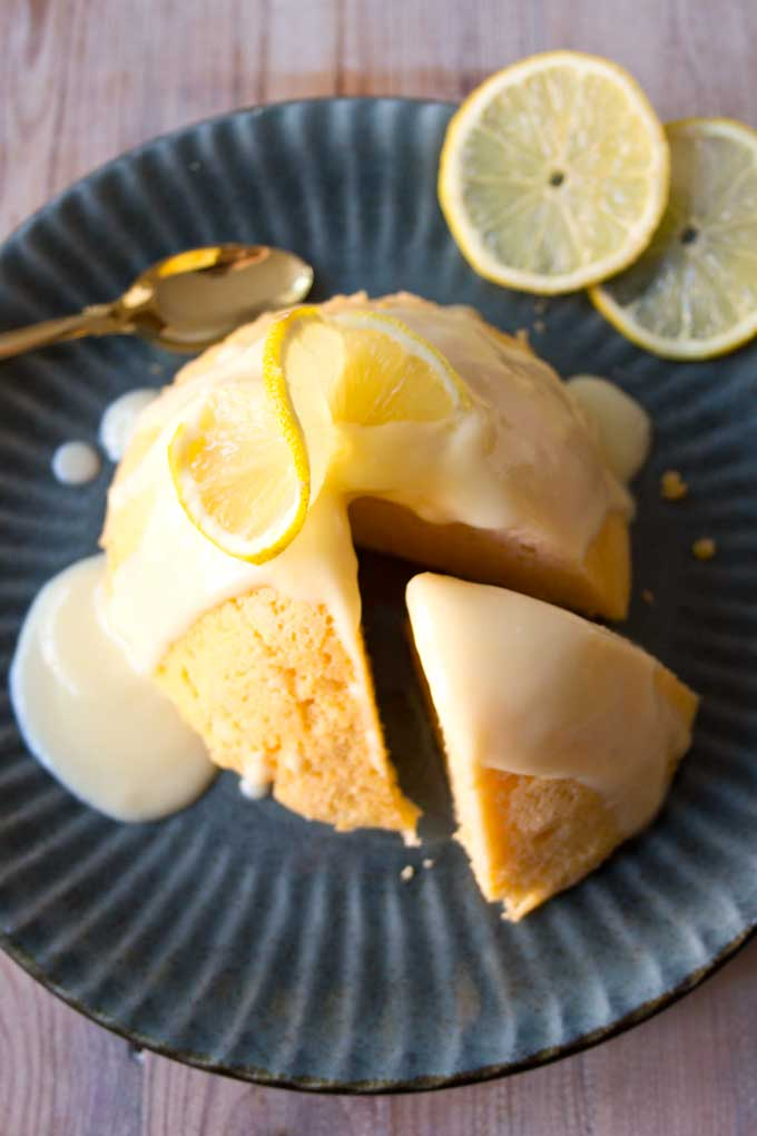 A sugar free lemon mug cake on a plate with a spoon and lemon slices