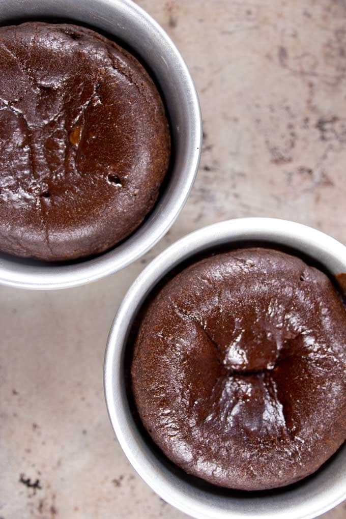 2 baked chocolate lava cakes in ramekins after baking