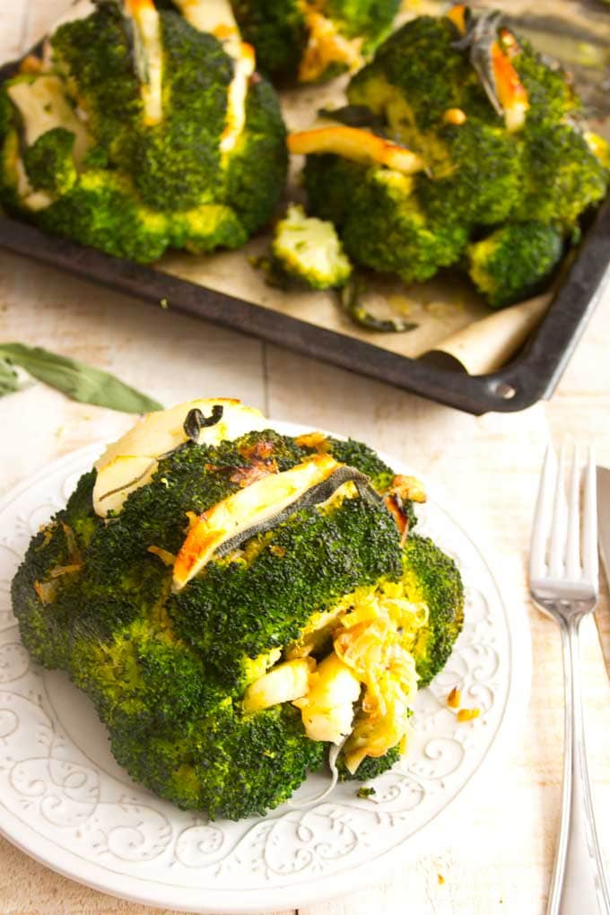 a roasted broccoli head on a plate with a tray full of more broccoli heads in the background