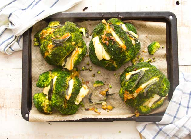 a baking tray with four roasted broccoli heads