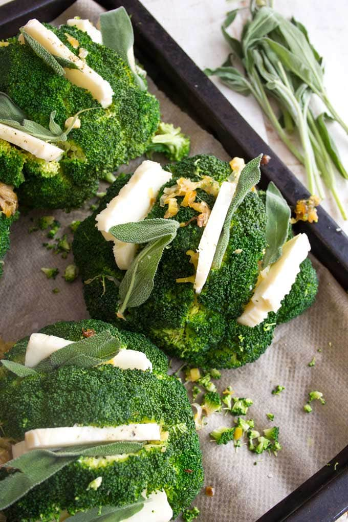 broccoli heads with halloumi and sage on a baking tray before baking