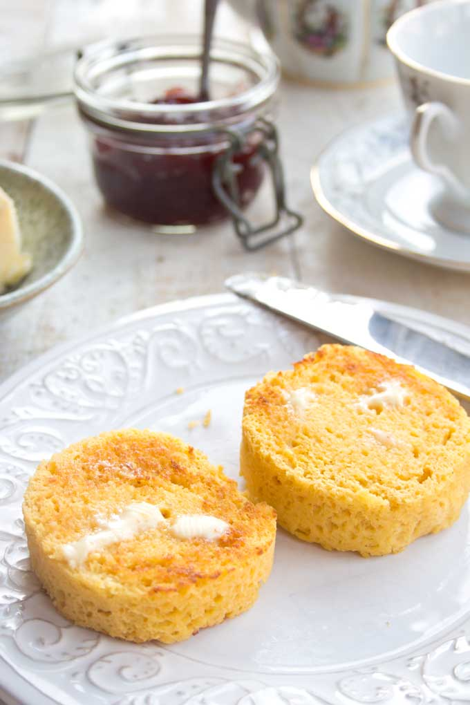 2 buttered muffin slices on a plate with a cup and jam