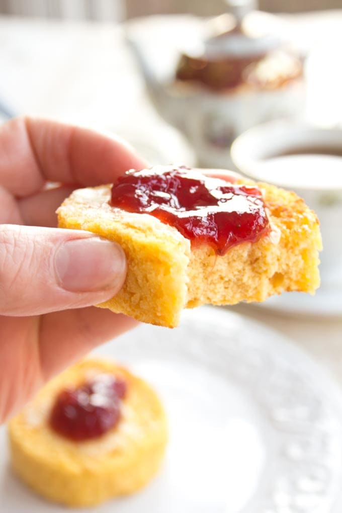 Closeup of a hand holding an English muffin with butter and jam