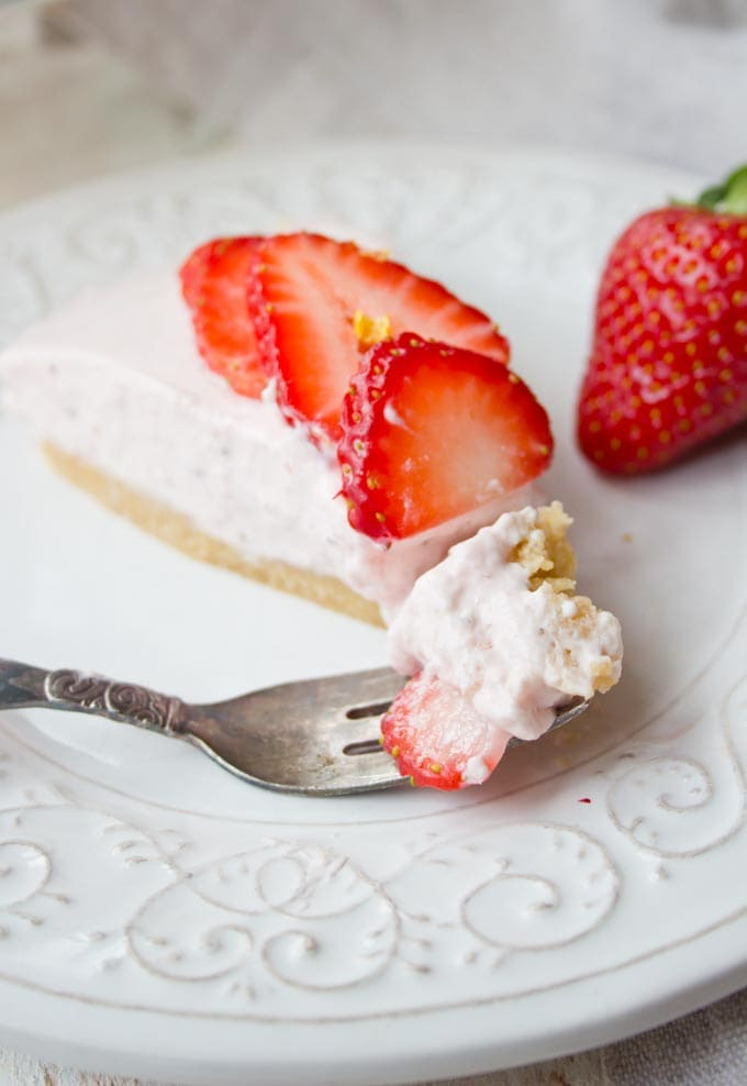 A slice of strawberry cheesecake on a plate and a fork