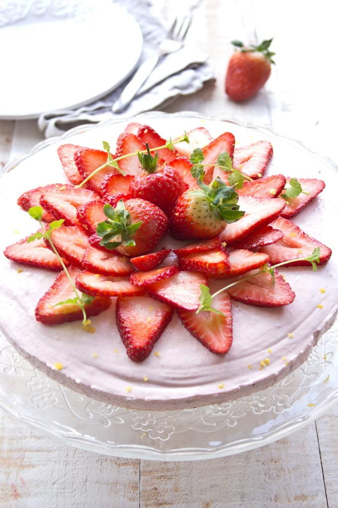 A low carb strawberry cheesecake on a cake stand