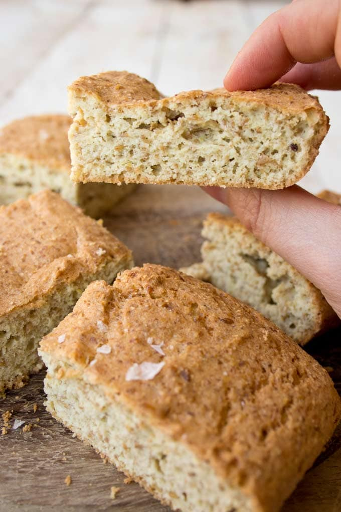 Hand holding a slice of coconut flour flaxseed bread