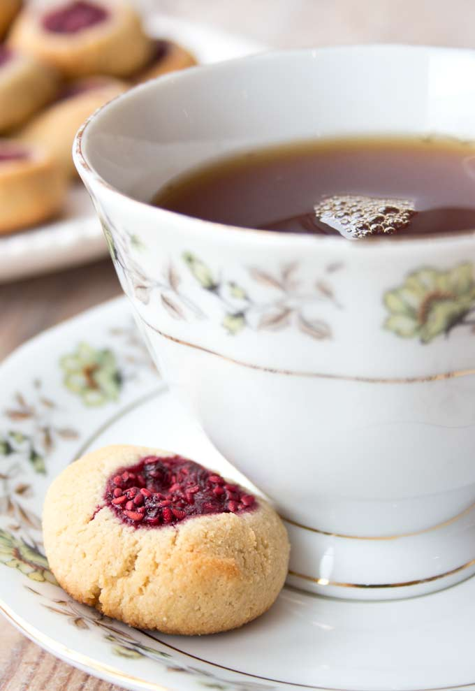 A low carb raspberry thumbprint cookie on a saucer with a cup of tea