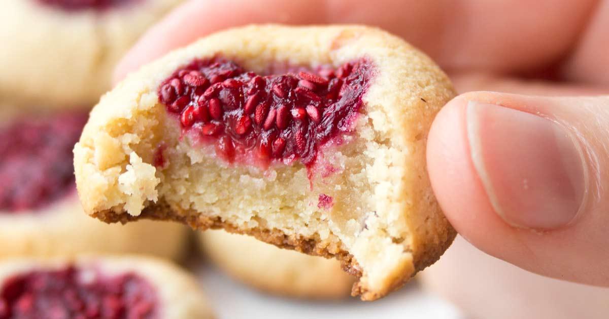 a raspberry thumbprint cookie bitten