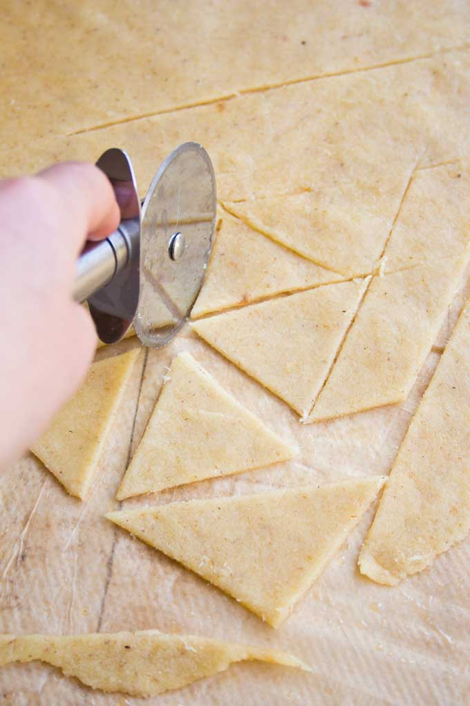Cutting low carb tortilla chips triangles with a pizza cutter
