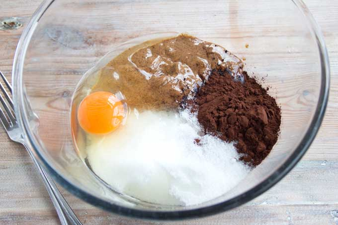 Bowl with ingredients for almond butter brownie cookies - egg, almond butter, cocoa, sweetener
